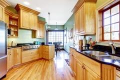 A luz tonifica armários de cozinha com parte superior contrária preta Imagens de Stock Royalty Free