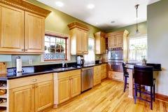 A luz tonifica armários de cozinha e a tabela pequena com cadeiras Fotografia de Stock