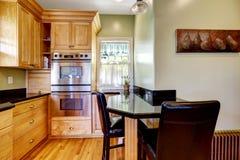 A luz tonifica a sala da cozinha com mesa de jantar e as cadeiras pequenas Fotos de Stock