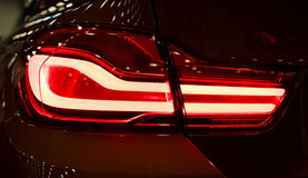 Luz traseira vermelha em um carro moderno com reflexão Do close up o carro vermelho da luz da cauda para trás Foto de Stock