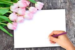 Luz - tulipas cor-de-rosa na tabela do marrom do carvalho com a folha branca do pap Imagem de Stock