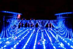 Luz ultravioleta en la tabla con los vidrios de cóctel vacíos Imágenes de archivo libres de regalías
