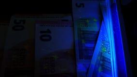 Luz UV usando-se para verificar euro- cédulas Detecção do dinheiro falso filme