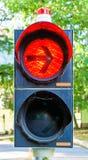 Luz vermelha em um sinal com uma seta que proibe os veículos que desejam girar certo de continuar sua viagem foto de stock