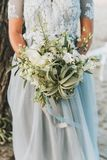 Luz vestindo da noiva - ramalhete azul da terra arrendada do vestido de casamento foto de stock