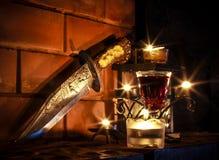 Luz y daga de Candels en la chimenea Foto de archivo