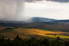 Luz y tormenta sobre los campos de Toscana Foto de archivo
