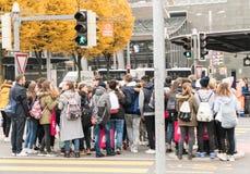 Luzerne, LU/Zwitserland - November 9, 2018: vele voetgangers overbevolken een kruisingseiland bij een bezige weg en zebrapad tijd stock afbeelding