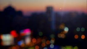 Luzes abstratas borradas do fundo, foco bonito da mudança da opinião da arquitetura da cidade na noite 4K filme