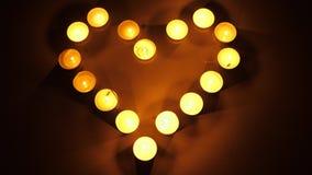 Luzes ardentes do chá do formulário do coração Velas claras do chá que formam a forma de um coração Conceito do tema do amor filme
