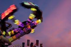 Luzes coloridas do borrão de movimento do passeio do carnaval no crepúsculo Imagens de Stock