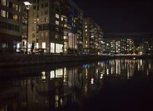 Luzes da cidade refletidas na água Silhueta sob um revérbero fotografia de stock royalty free