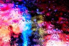 Luzes de néon atrás das gotas da água perto acima fotografia de stock royalty free