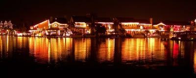 Luzes de Natal das casas que refletem no lago Fotografia de Stock Royalty Free