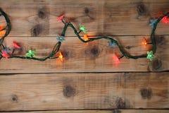 Luzes de Natal em um fundo de madeira Fotos de Stock