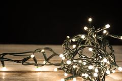 Luzes de Natal na forma da bola na mesa de madeira retro imagem de stock