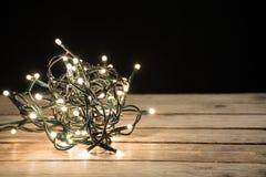 Luzes de Natal na forma da bola na mesa de madeira retro e no fundo preto imagens de stock royalty free