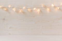 Luzes de Natal que queimam-se em um fundo de madeira branco Imagens de Stock Royalty Free