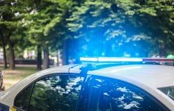 Luzes de piscamento do carro de polícia contra o parque do verde da cidade fotografia de stock royalty free