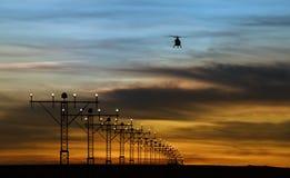 Luzes de pista de decolagem e silhueta de um helicóptero Fotografia de Stock Royalty Free