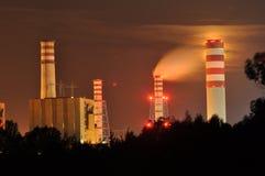 Luzes de poder iluminadas na noite Chaminés que lançam o fumo Guindastes, estendendo o elétron Geração de calor Imagens de Stock
