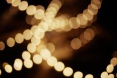 Luzes defocused da decoração do bokeh do borrão do vintage da cor dourada no fundo preto Foto de Stock Royalty Free