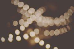 Luzes defocused da decoração do bokeh retro do borrão da cor dourada no fundo preto Fotografia de Stock Royalty Free