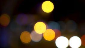 Luzes Defocused ou macias do bokeh do foco dos carros, dos 'trotinette's, dos velomotor e do tráfego conduzindo em ruas da cidade filme
