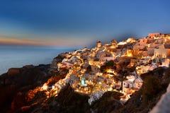 Luzes do início da noite em Oia Santorini, ilhas de Cyclades Greece Fotografia de Stock