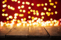 Luzes douradas abstratas borradas do ponto com madeira Imagens de Stock