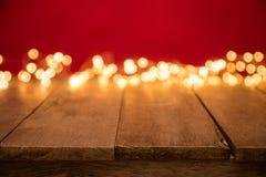 Luzes douradas abstratas borradas do ponto com madeira Fotografia de Stock Royalty Free