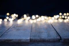 Luzes douradas abstratas borradas do ponto com madeira Fotos de Stock Royalty Free