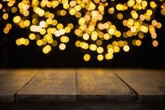 Luzes douradas abstratas borradas do ponto com madeira Imagem de Stock