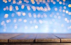 Luzes douradas abstratas borradas do ponto com madeira Foto de Stock Royalty Free
