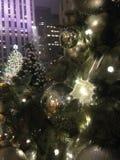 Luzes e ornamento da bola em uma árvore de Natal com gotas da chuva após a chuva na noite Imagens de Stock Royalty Free
