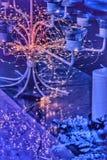 Luzes em torno de um castiçal de vidro luxuoso, uma noite festiva da festão, fundo azul, luzes mornas de incandescência fotografia de stock