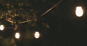 Luzes exteriores da corda do partido que penduram em uma linha no quintal Tiro da zorra filme