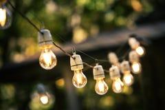 Luzes exteriores da corda que penduram em uma linha Fotos de Stock