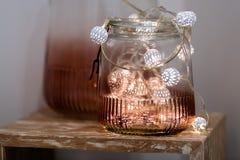 Luzes feericamente brancas e cor-de-rosa do chá no frasco de vidro colorido com fundo borrado imagem de stock