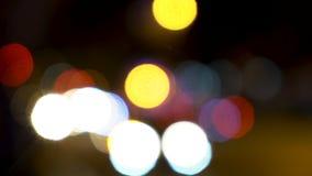 Luzes macias do bokeh do foco dos carros, dos 'trotinette's, dos velomotor e do tráfego conduzindo em ruas da cidade na noite vídeos de arquivo