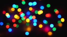 Luzes Multi-coloridas twinkling borradas do feriado no fundo preto filme