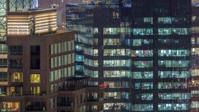 Luzes nas janelas do prédio de escritórios múltiplo moderno da história no ajuste urbano no timelapse da noite filme
