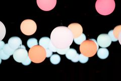 Luzes redondas coloridas do pendente do globo suspendidas no backround escuro imagens de stock