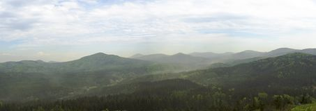 Luzicke hory mountains wide panorama, skyline view from hill stredni vrch, green forest and blue sky. White clouds background Stock Photo