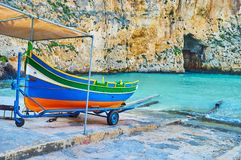 Luzzu boat at Dwejra Inland sea, San Lawrenz, Gozo, Malta. The colored wooden Maltese luzzu boat on shore of Dwejra Inland sea with a view on Blue Hole grotto on stock images