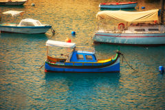 Luzzu boat moored in the harbour at sunset time. Malta. The traditional maltese Luzzu boat moored in the harbour at sunset time. Malta Stock Photos