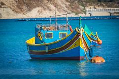 Luzzu Marsaxlokk harbour. Traditional colourful Maltese Luzzu fishing boats in the turquoise blue water of Marsaxlokk harbour, Marsaxlokk, Malta, June 2017 Royalty Free Stock Image