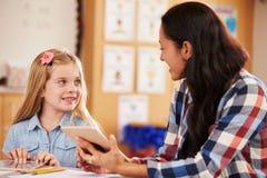 Élève et professeur d'école primaire à l'aide de la tablette Photographie stock