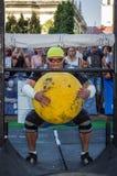LVIV, ΟΥΚΡΑΝΊΑ - ΤΟΝ ΑΎΓΟΥΣΤΟ ΤΟΥ 2017: Ένας ισχυρός αθλητής ένα bodybuilder ανυψώνει μια τεράστια βαριά κίτρινη σφαίρα πετρών στ Στοκ Εικόνα