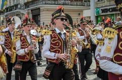 LVIV, ΟΥΚΡΑΝΊΑ - ΤΟ ΜΆΙΟ ΤΟΥ 2018: Μια ορχήστρα πνευστ0ών από χαλκό με τα τύμπανα στα κοστούμια καρναβαλιού περπατά στο κέντρο τη Στοκ Εικόνες
